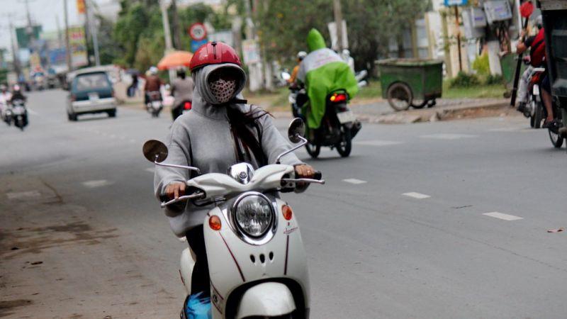 Từ sáng sớm, nhiều người đi đường phải bịt kín, mặc áo dày vì nhiệt độ xuống thấp - Ảnh: Mậu Trường
