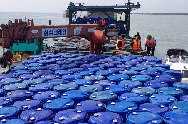 Lực lượng chức năng kiểm tra các thùng phuy chứa dầu nhớt trên sà lan.