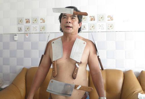 Ông Tài với 6 con dao inox dán xung quanh người. Ảnh: PT