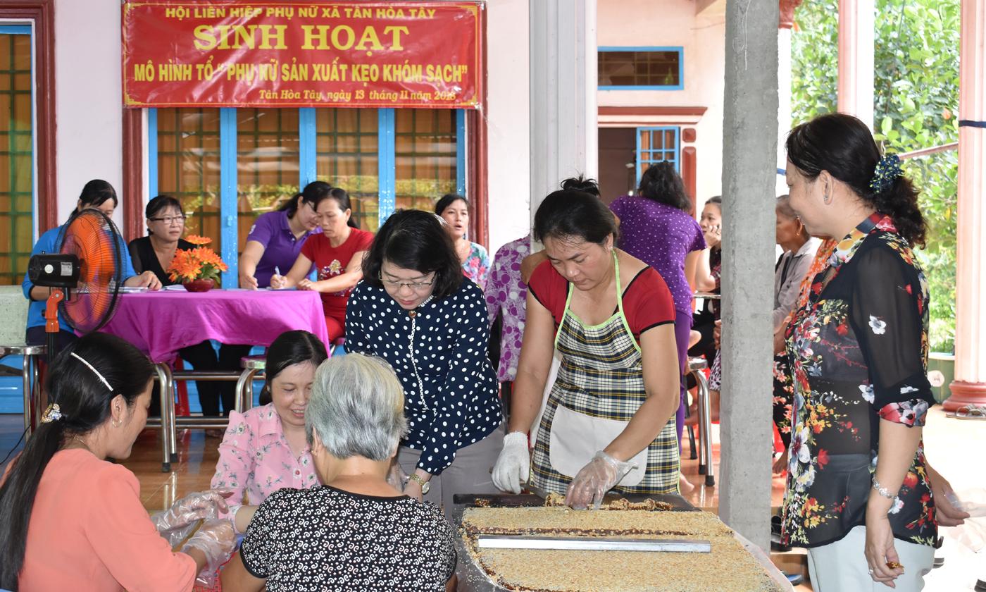 Chị em phụ nữ tham quan quy trình sản xuất kẹo khóm sạch của Tổ sản xuất kẹo khóm sạch