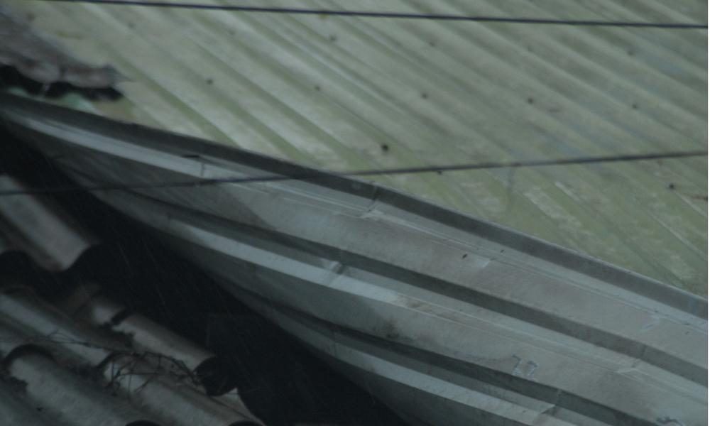 Tấm tol của nhà một hộ dân bị gió thổi bung lên trong bão.