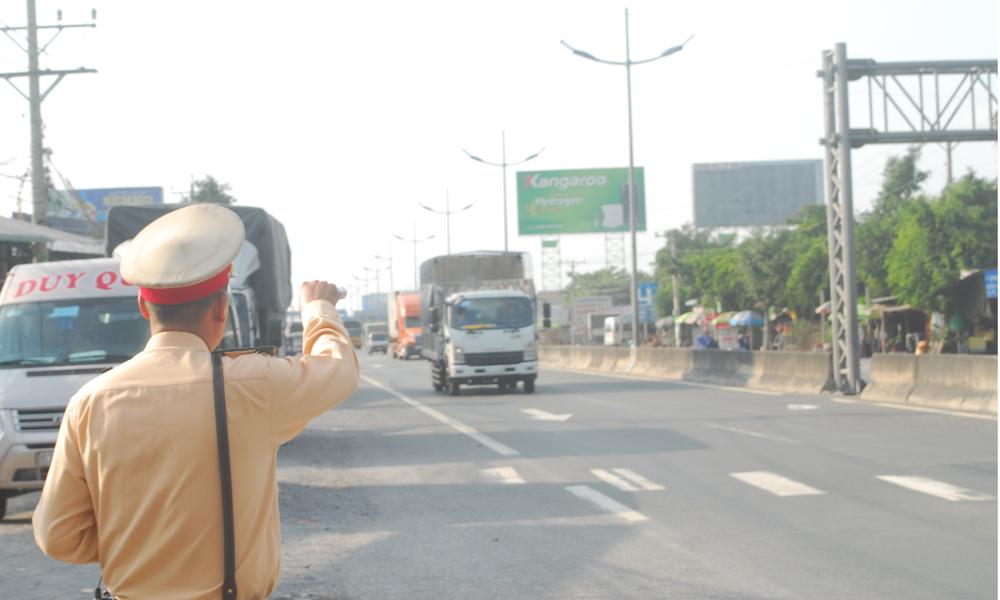 Cảnh sát giao thông ra hiệu lệnh yêu cầu tài xế chở heo dừng xe để kiểm tra.