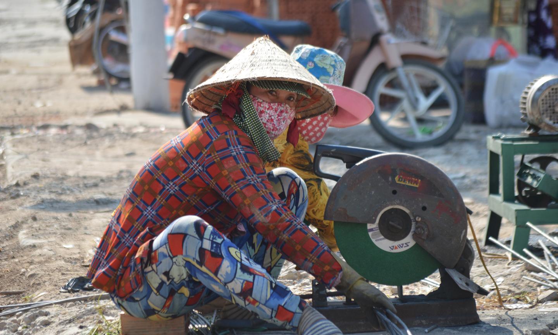 Hai nữ thợ hồ dưới cái nắng hắt lên từ mặt đường Ngô Quyền, TP.Mỹ Tho.