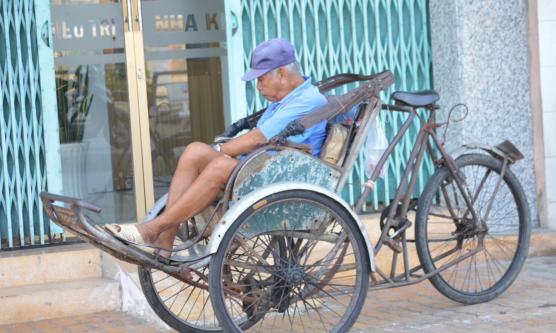 Ông lão tranh thủ chợp mắt cùng với chiếc xe xích lô.