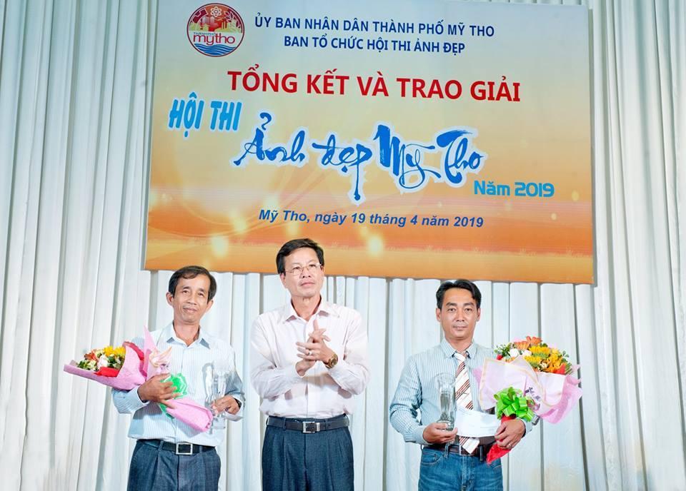 Phó giám đốc Sở VH-TT-DL Tiền Giang Lê Văn Dũng trao giải cho tác giả Võ Nguyên Phú (trái) và Nguyễn Hoàng Nam.