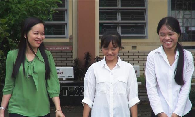 Em Trần Thúy Vy (giữa) và Lâm Lê Thanh Tuyền cùng cô giáo chủ nhiệm lớp 12C1 Bùi Thị Bích Vân. Ảnh: Hồng Đạt/TTXVN