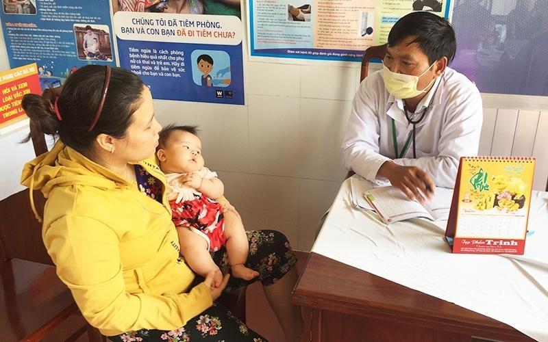 Các y, bác sĩ Trạm y tế xã Cư Êbur, TP Buôn m-a Thuột (Đăk Lăk) hướng dẫn người dân cách phòng, chống bệnh sốt xuất huyết cho con. Ảnh: Báo Nhân dân