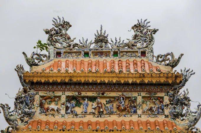 Trên tầng mái cổng tam quan được trang trí tinh xảo các tượng long, lân, quy, phượng, canh, mục, ngư tiều... Vật liệu bằng đồ sứ của Việt Nam, Trung Hoa với nước men xanh tạo nên màu sắc óng ánh.